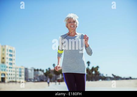 Senior woman power walking on beach - Stock Photo
