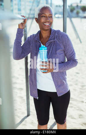 Woman in sportswear leaning on bar at beach playground - Stock Photo
