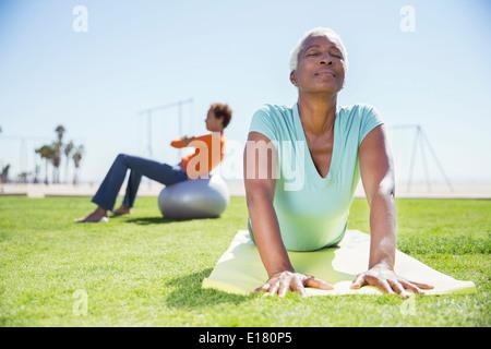 Women practicing yoga in sunny park - Stock Photo