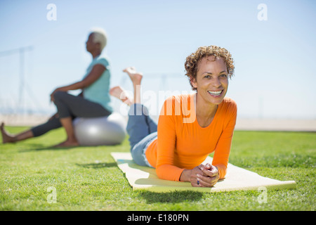 Portrait of smiling woman on yoga mat in park - Stock Photo
