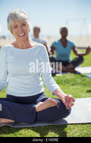 Portrait of smiling senior woman practicing yoga in park - Stock Photo
