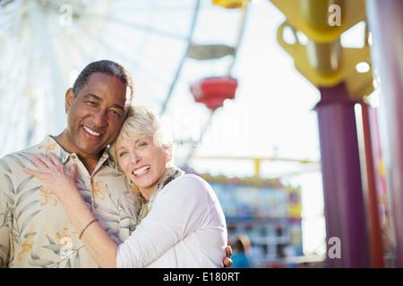 Portrait of smiling senior couple at amusement park - Stock Photo