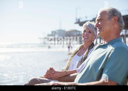 Senior couple relaxing on sunny beach - Stock Photo