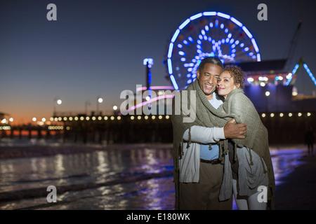 Couple hugging on beach at night - Stock Photo