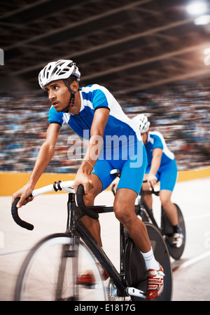 Track cyclists riding in velodrome - Stock Photo
