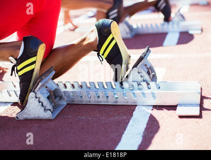 Runner's feet in starting blocks on track - Stock Photo