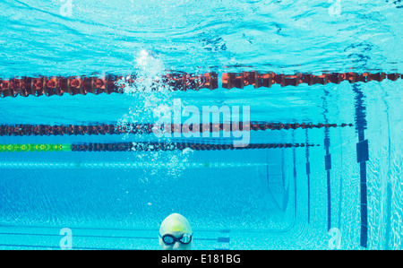 Swimmer smiling underwater in swimming pool - Stock Photo