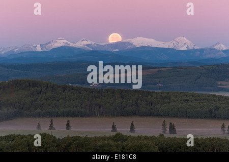 Full Moon setting over Rocky Mountains, taken from Rothney Astrophysical Observatory on August 28, 2007, night of - Stock Photo