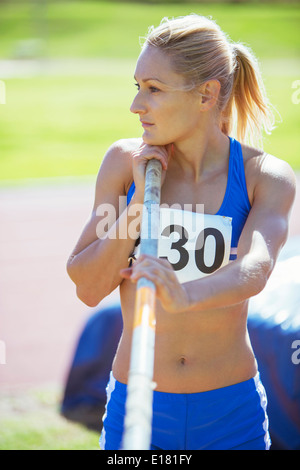 Track and field athlete holding pole - Stock Photo