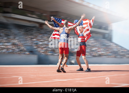 Runners celebrating and holding American flags on track - Stock Photo