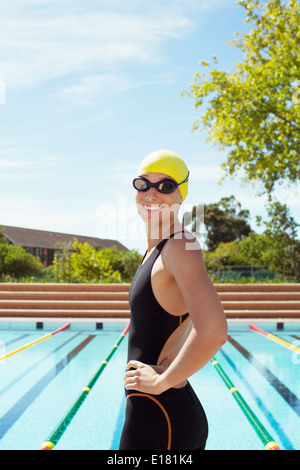 Portrait of smiling swimmer at poolside - Stock Photo