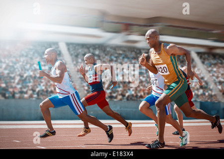 Relay runners racing on track - Stock Photo