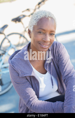 Portrait of smiling woman near bicycle - Stock Photo