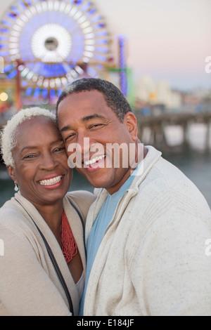 Portrait of happy senior couple at amusement park - Stock Photo