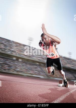 Sprinter taking off from starting block - Stock Photo