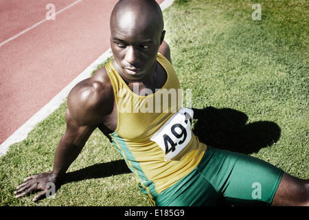 Athlete resting in grass next to running track - Stock Photo