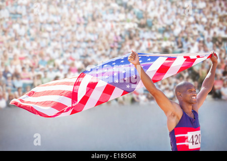 Track and field athlete holding American flag in stadium - Stock Photo