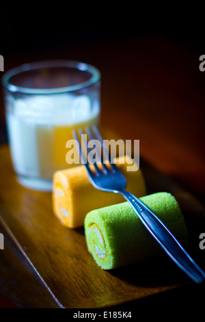 "Two ""Swiss rolls"" slices green orange yellow on a tray have a fork on top with fresh Plain milk in glass - Stock Photo"