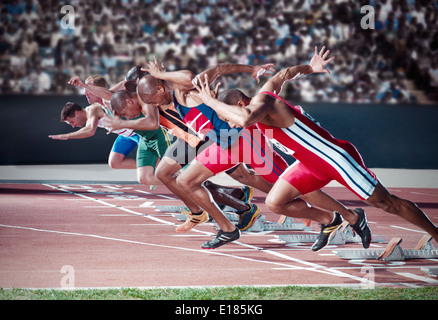 Runners taking off from starting blocks on track - Stock Photo