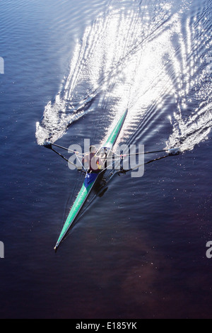 Man rowing scull on lake - Stock Photo