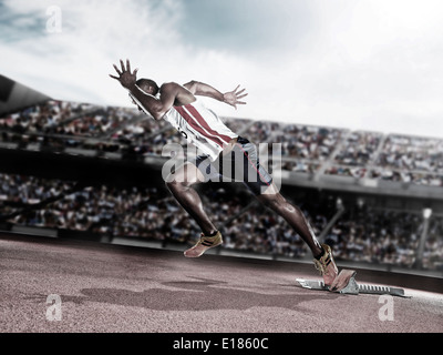 Runner taking off from starting block on track - Stock Photo