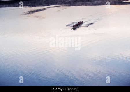 Rowing crew rowing scull on lake in distance - Stock Photo