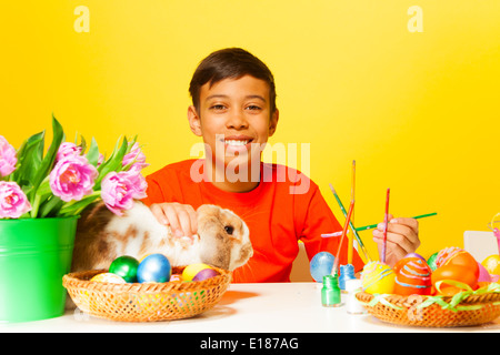 Boy paints Easter eggs with rabbit on the table - Stock Photo