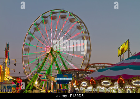 Carnival ferris wheel in motion with bright neon lights at dusk. - Stock Photo