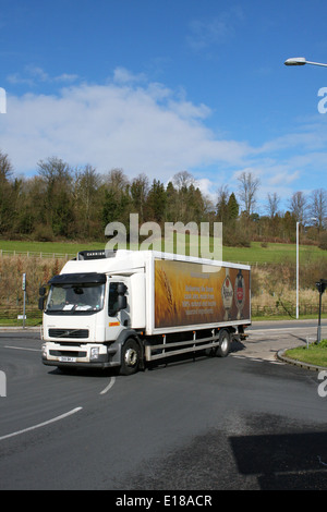 A DHL truck, with JD Wetherspoons advertising entering a roundabout in Coulsdon, Surrey, England - Stock Photo