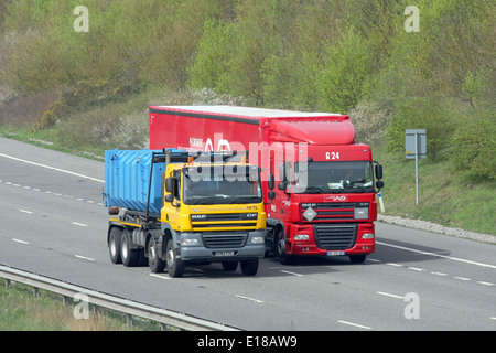 A Southern Water truck overtaking a Norbert Dentressangle truck on the M20 motorway in Kent, England - Stock Photo
