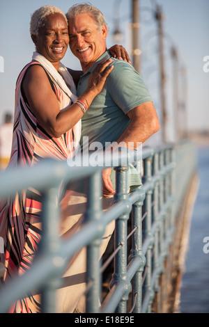 Portrait of smiling senior couple hugging on pier - Stock Photo