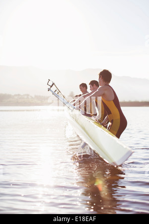 Rowing team placing boat in lake - Stock Photo