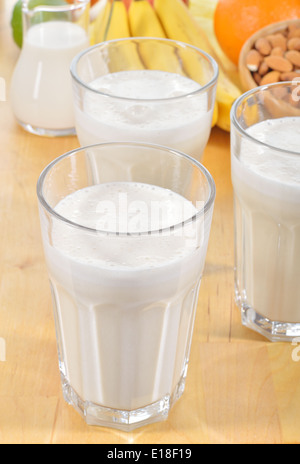 Banana and almond milk smoothie in a glass on a kitchen table. Summer drink made of banana, almond milk and few - Stock Photo