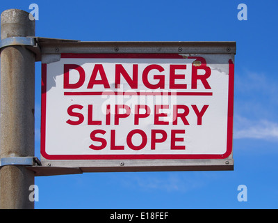 Sign proclaiming 'Danger Slippery Slope' against a blue sky - Stock Photo