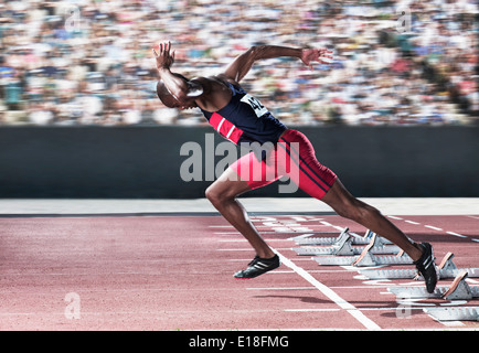 Sprinter taking off from starting block on track - Stock Photo