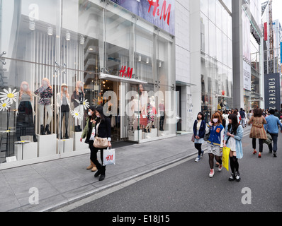 Young people walking on streets in one of Tokyo's fashion districts. HM and Forever 21 fashion clothing stores in - Stock Photo