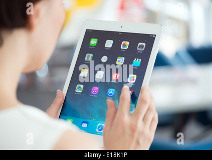 Woman holding brand new white Apple iPad Air, the most advanced digital tablet in part of the iPad line - Stock Photo