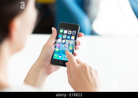 Woman holding brand new black Apple iPhone 5S, the most advanced smartphone in part of the iPhone line - Stock Photo