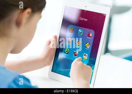 Little girl looking on a brand new Apple iPad Air with various game applications on a screen - Stock Photo