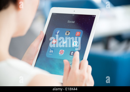 Woman looking on social media applications on modern white Apple iPad Air - Stock Photo