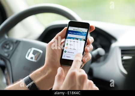 Man in a car planning a trip using Tripadvisor app on Apple iPhone 5S - Stock Photo