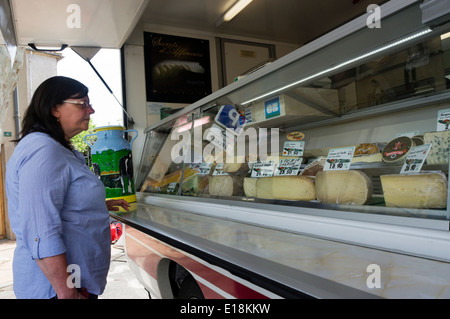 A woman buying cheese from a travelling cheese van on a French market. - Stock Photo