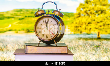 Clock on Bible in front of monitor - Stock Photo
