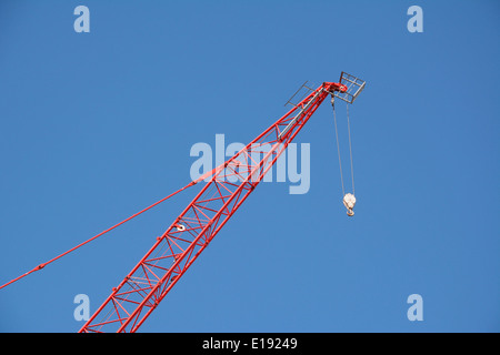 Red crane boom reaching up high against a clear blue sky - Stock Photo