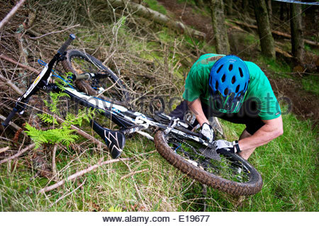 A mountain biker attempts to fix his deraileur and drive train while competing during the UK Gravity enduro in the - Stock Photo