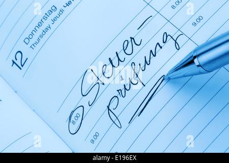 Ein Termin ist in einem Kalender eingetragen: Steuerpr¸fung - Stock Photo