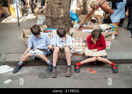 Children reading books and comics at a market in the Latin Quarter, Paris, France - Stock Photo