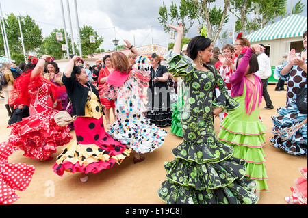 Women in colourful flamenco dresses dancing at the Seville April Fair, Spain - Stock Photo