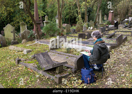 Artist painting in Highgate Cemetery, London, England, UK - Stock Photo