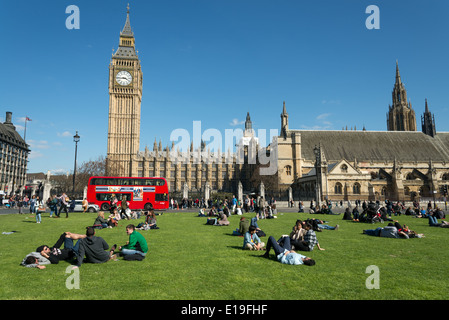People relaxing in Parliament Square, London, England, UK - Stock Photo
